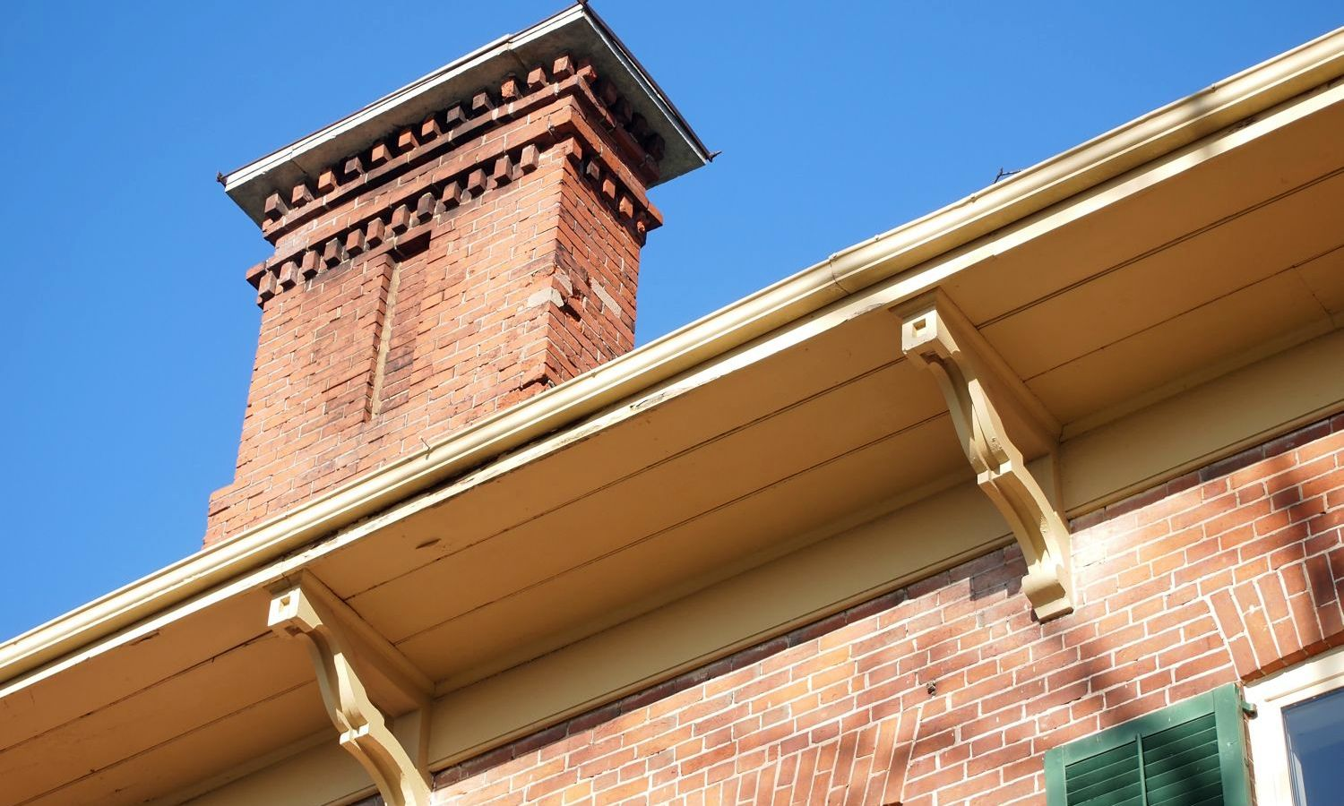 Detail of roof eave with brackets and brick chimney